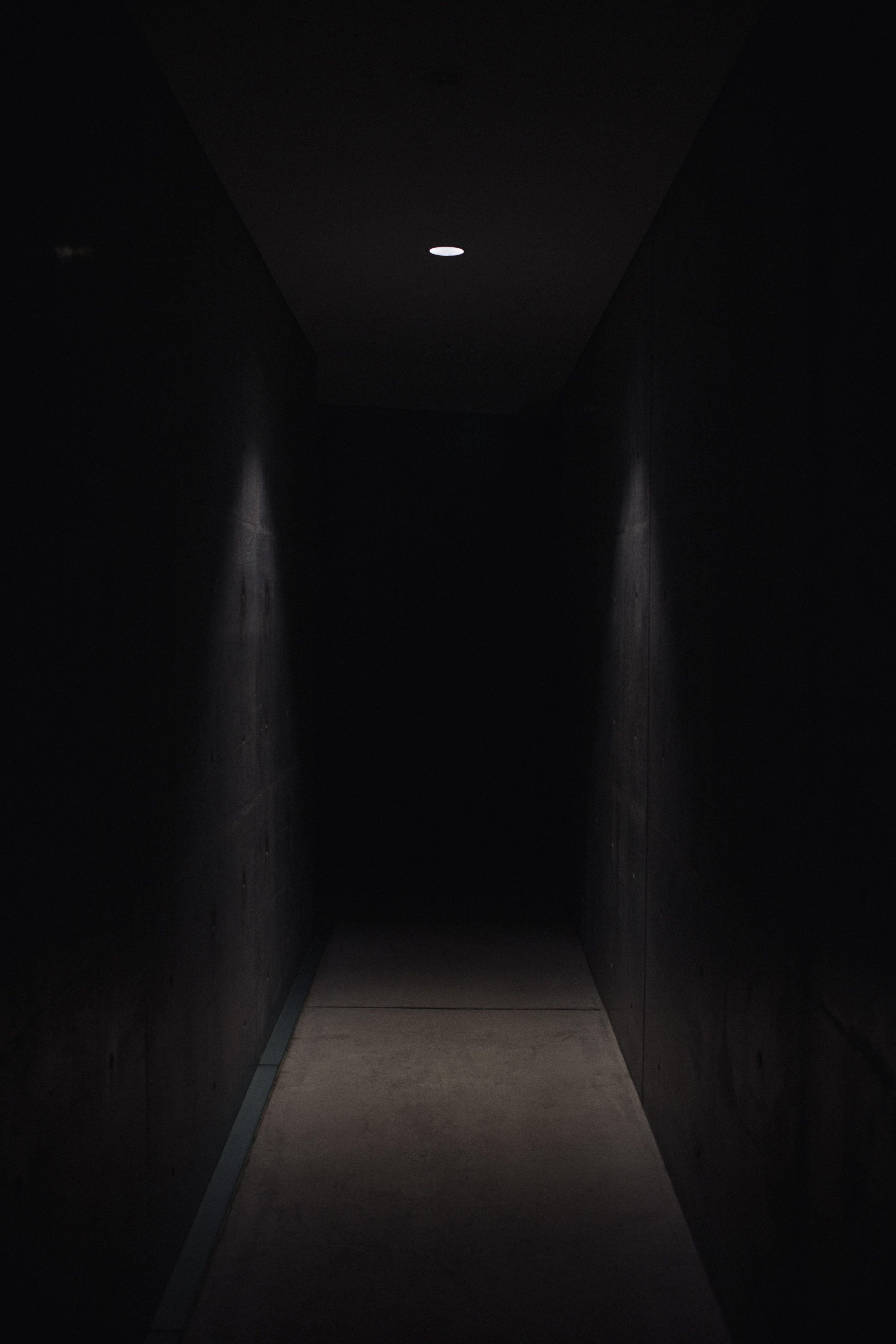 Dark Pathway Lit With Small Light Fixture Latar Belakang Lorong Gambar
