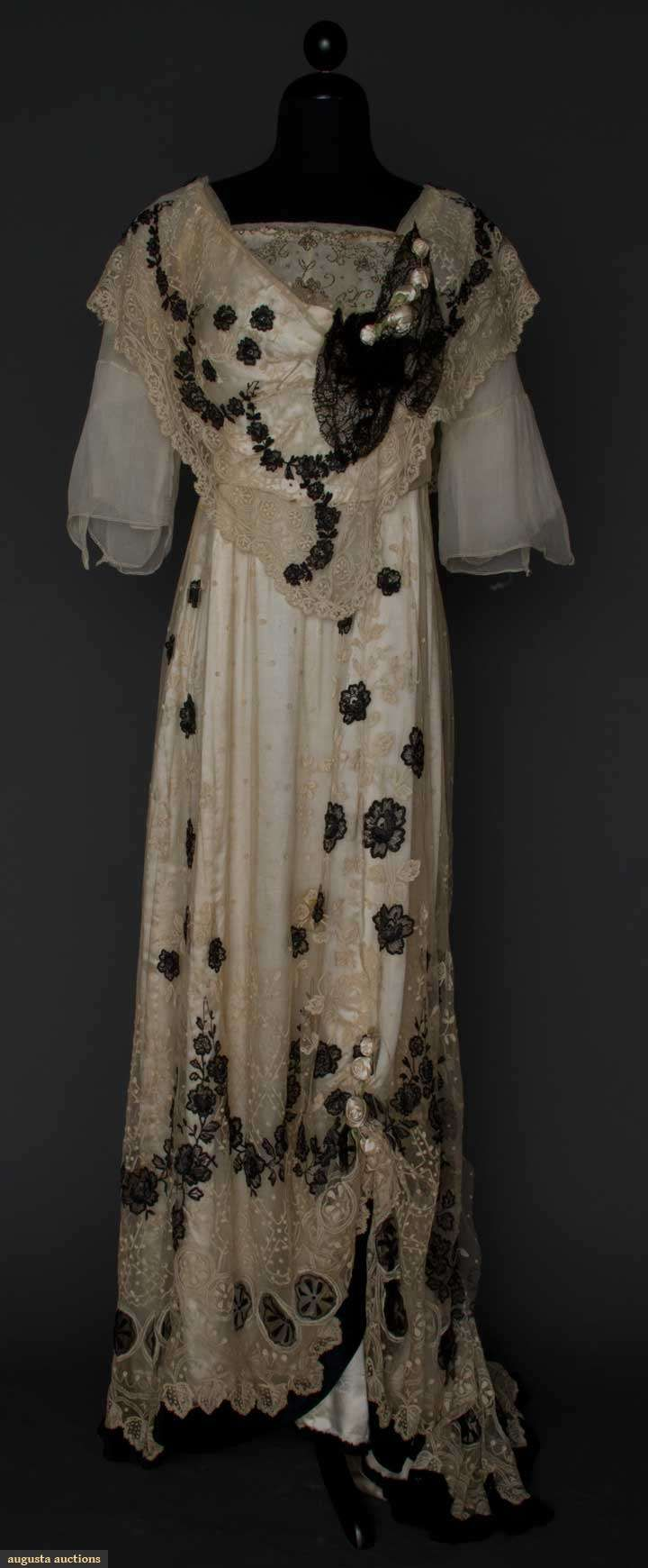 White silk satin evening dress with tambour-embroidered net overlay, black lace appliqué, and white silk ribbon rose-bud decoration, c. 1912.