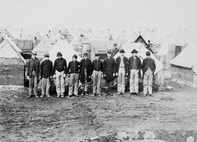 A Group of Union Soldiers Posing in Front of Their Winter Quarters Near City Point, Virginia (1864)