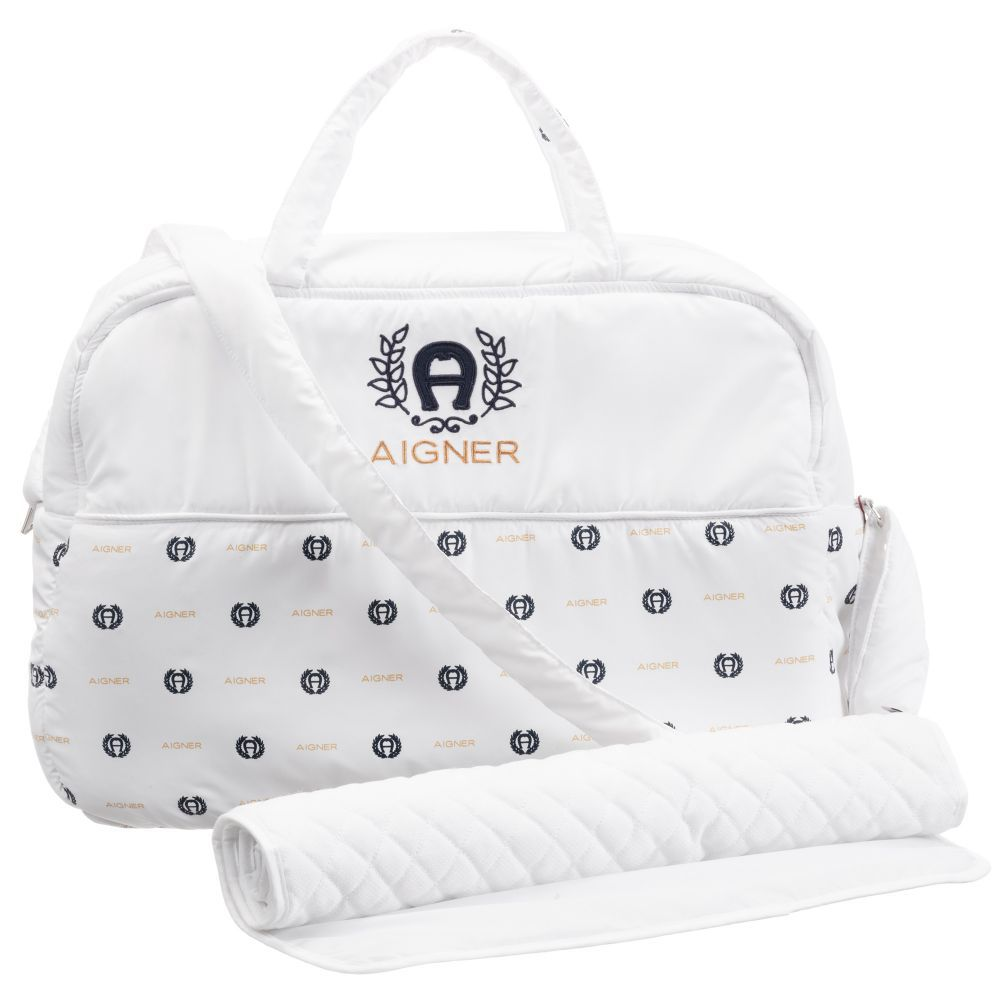 f1017909b9 White fabric baby changing bag by Aigner Kids, with a blue crest print and  embroidered logo. There are two carry handles, top zip closure, and an  adjustable ...