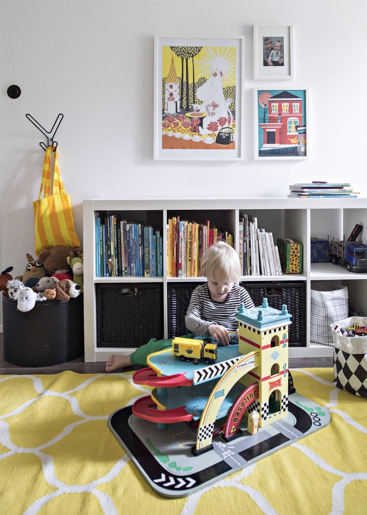 Päiväkodin jälkeen Niilo jatkaa leikkejä kotonaan. Lastenhuoneen hylly ja matto ovat Ikeasta. Kehyksissä on TaiKin joulumyyjäisistä ostettuja talvikuvia. Muumikuva on Niilon kummitädiltä.
