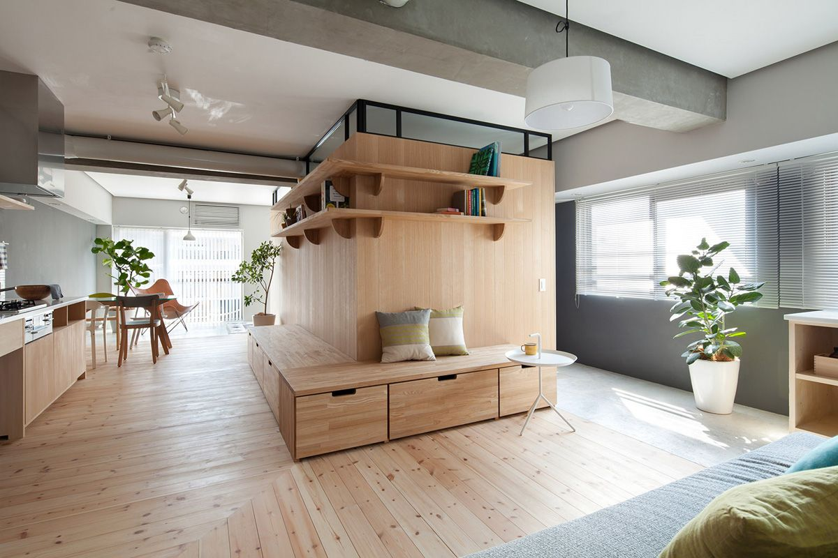 Tokyo architecture studio Sinato refurbishes this 64 sqm apartment in Yokohama adding a wall in the centre that incorporates shelves, a seating area and storage space, and encloses the master bedroom and a guest bedroom behind it.