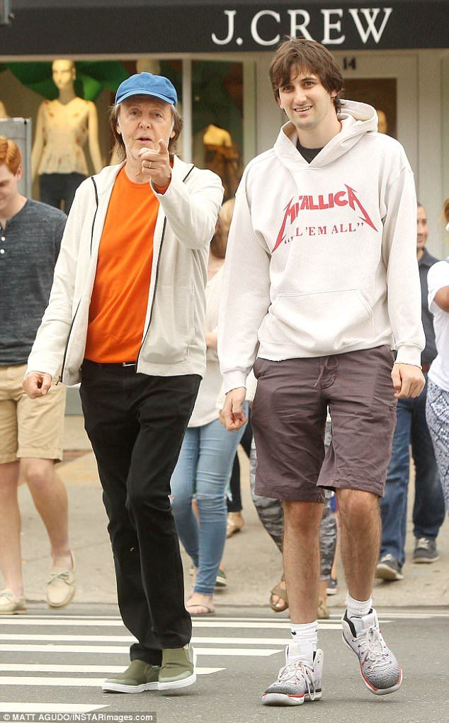 British Musician Paul 75 Caught The Eye In His Striking Orange Tee As He Enjoyed A Relaxed Spot Of Shopping With Step Son