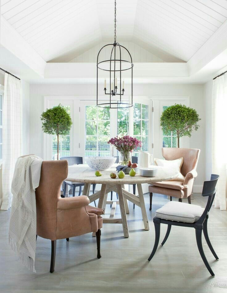 Airy sunroom with round table and mismatched chairs ...