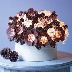 "Pinecone ""flowers"" with glowing centers fill a simple vase in this exquisite arrangement."