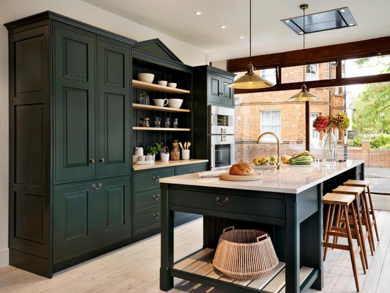 Dark Green Kitchen Storage With A Big Island And Dining Space In A