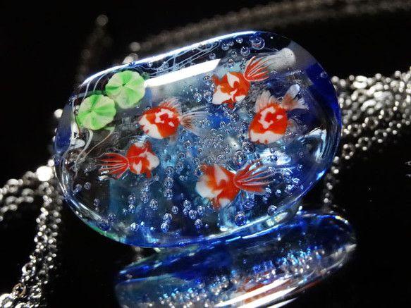バーナーワークの技法で制作した、手作りのガラスのネックレスです。水色と青を混ぜた地に、金魚を入れました。金魚は表面に描いたのではなく、ひとつずつパーツを作り、...|ハンドメイド、手作り、手仕事品の通販・販売・購入ならCreema。
