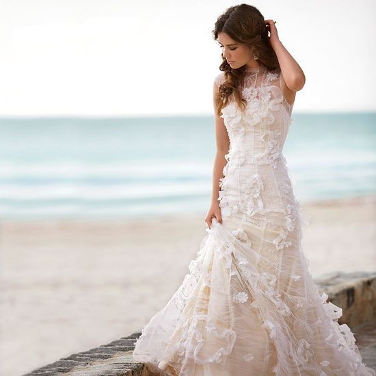 Consider adding a subtle touch of color to your beach wedding dress. This gorgeous mermaid gown by Reem Acra is made of peach and ivory lace and topped with organza flowers.
