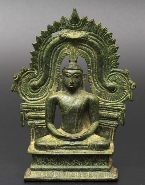 BUDDHA SRI LANKA. CA 17°-18° SIÈCLE Alliage cuivreux. H. 14,5 cm Rare représentation classique du Buddha assis en position de méditation sur une base quadrangulaire, devant un dosseret caractéristique du style local. Patine oxydée.