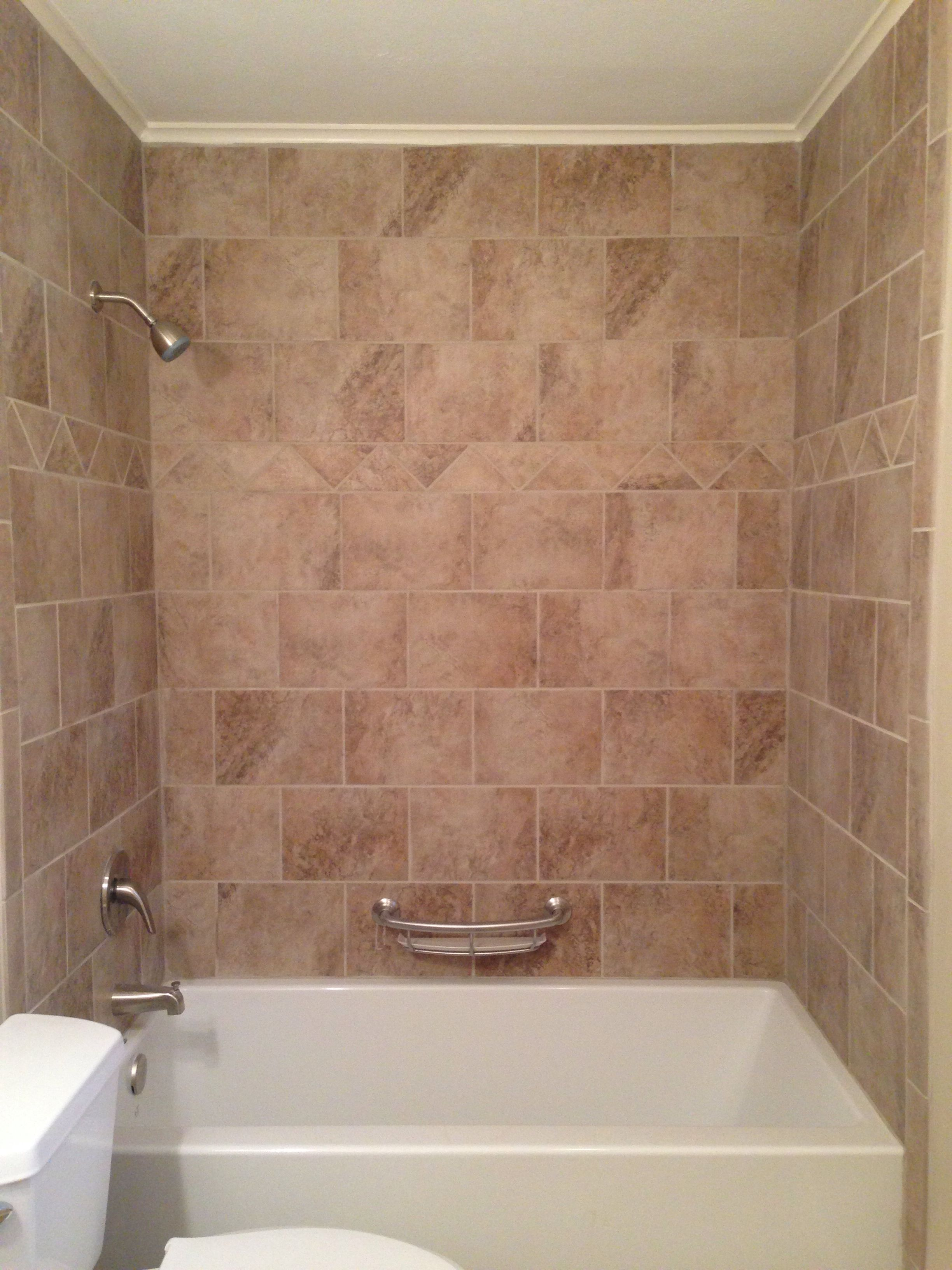 Tile surround bathtub. Beige tile around bathtub.