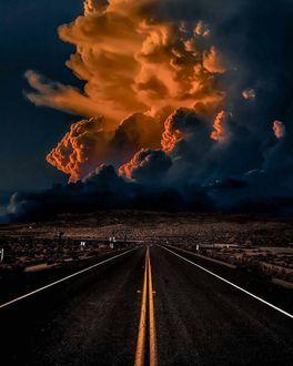 Фото Дорога с разметкой, ведущая вдаль, где на небе огромное облако