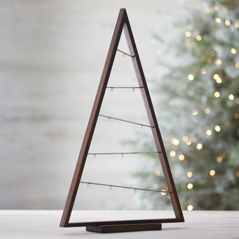 A simply styled triangle of natural shesham wood features diagonal metal bars with hooks to dangle a collection of ornaments in an implied tree shape. Wood and metalNatural oil finishClean with a dry clothMade in India.