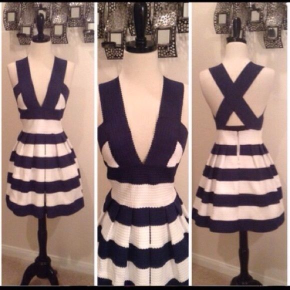 NAVY BLUE & WHITE PEPLUM DRESS (NWOT) Navy blue stripes on white fabric. Silver zipper closure. Cross back straps. V- neck front. Made of 70% polyester and 30% spandex. NOTE: (See pics)There is a small snag on right strap in the back also at the lower back on the inside are some threads that have unraveled. Both defects are not really noticeable. Agaci Dresses