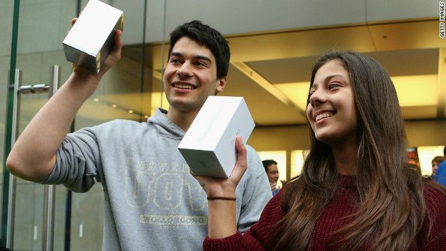 The first customers to purchase their new iPhone 5s exit an Apple flagship store on George street in Syndey, Australia