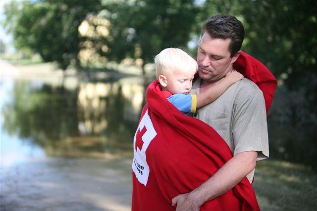 A Red Cross volunteer helps a little boy after a flood.