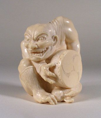 A fine Japanese ivory carving of a fierce looking, crouched oni with teeth barred in an wicked grin. Oni are creatures from Japanese folklore, variously translated as demons, devils, ogres or trolls. Popular characters in Japanese art, literature and theatre, they grew out of the religious traditions of Shintoism and Buddhism. This one holds a drum between his three-clawed hands while his feet are depicted with two claws each. A fine Tokyo School carving, it dates from the Meiji Period