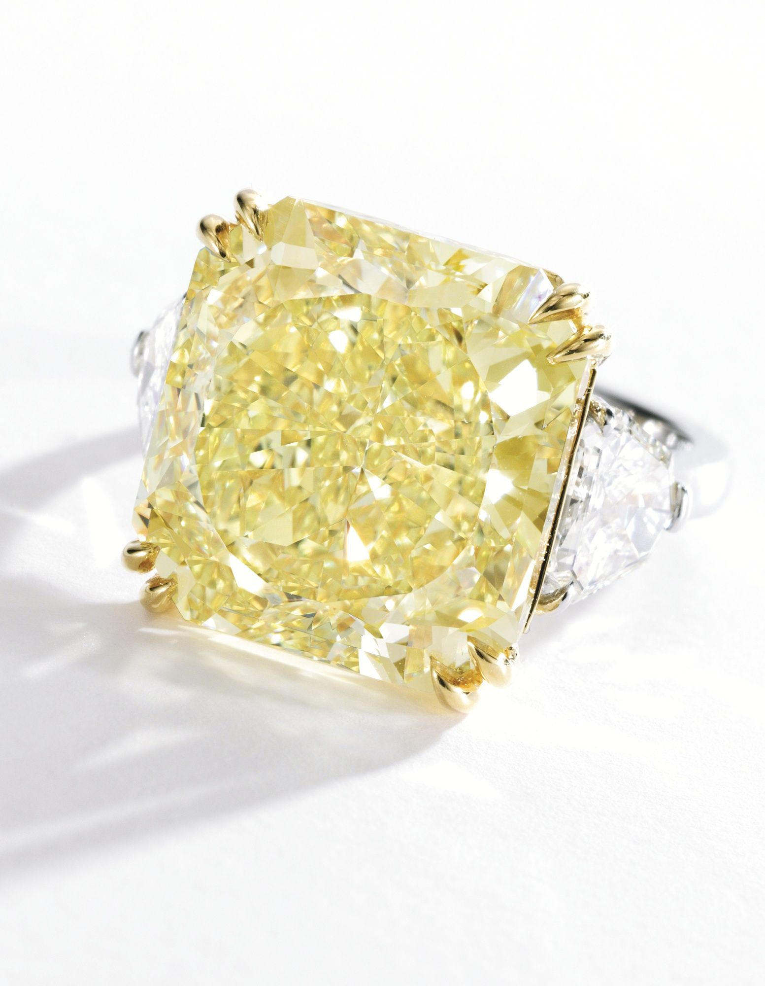 A very fine fancy vivid yellow diamond and diamond ring the cut