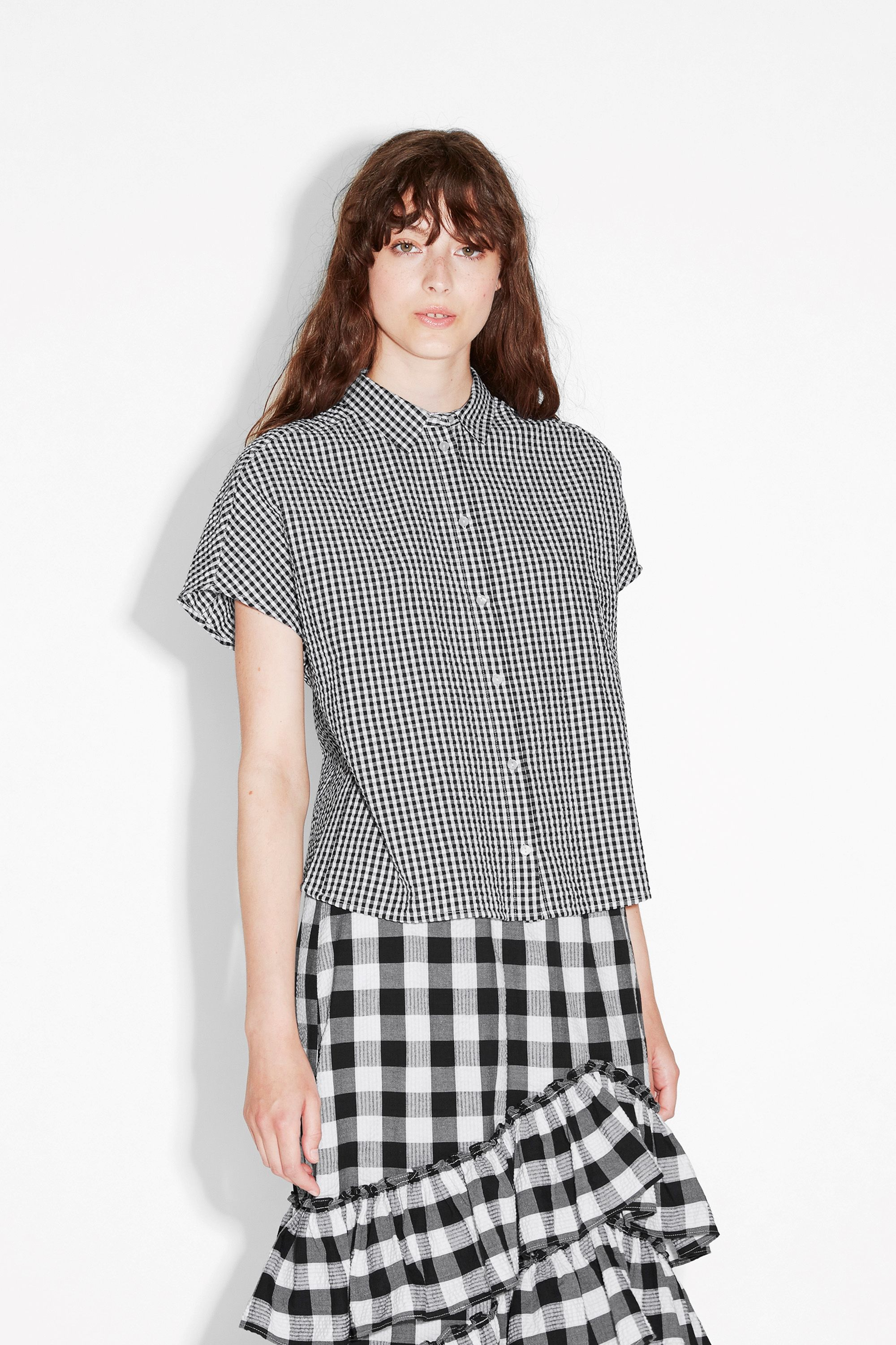 This button-up blouse gives us major summer feels. With its open back and seersucker cotton fabric, it's an airy beauty that'll keep you looking cute no matter how strong the sunbeams. colour: black magic  In a size small the chest width is 100 cm and the length is 59 cm. The model is 176 cm and is wearing a size small.