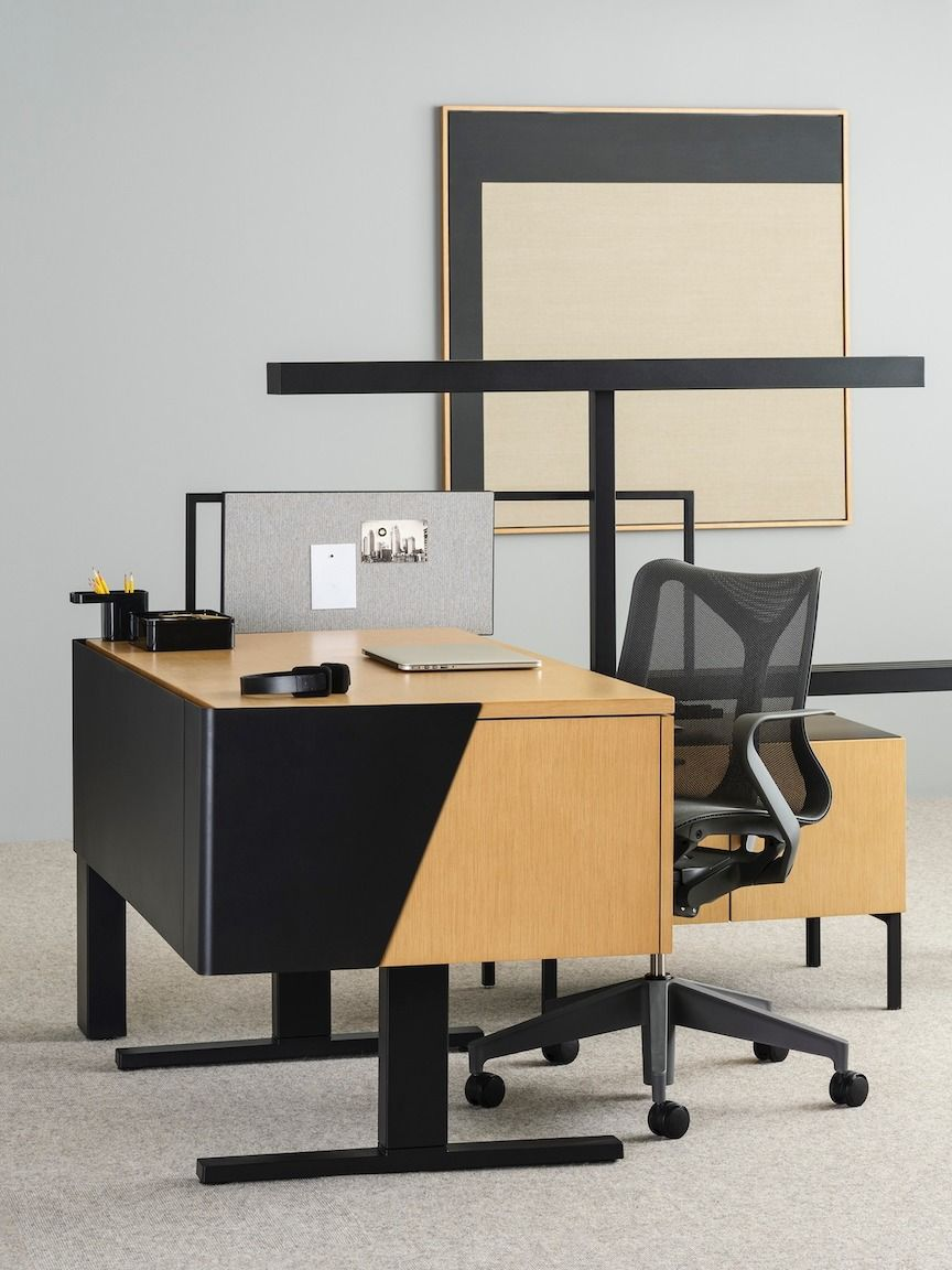 chair connected to desk geologic fishing neocon 2018 office herman miller wood a with geometric black accents low storage unit and metal t bar light dark gray cosm laptop computer