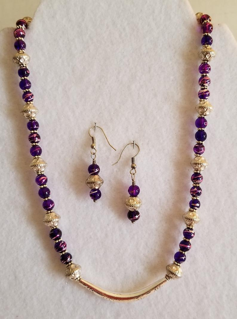 Necklace is made with purple glass beads and gold specer beads with a gold butterfly pendant.