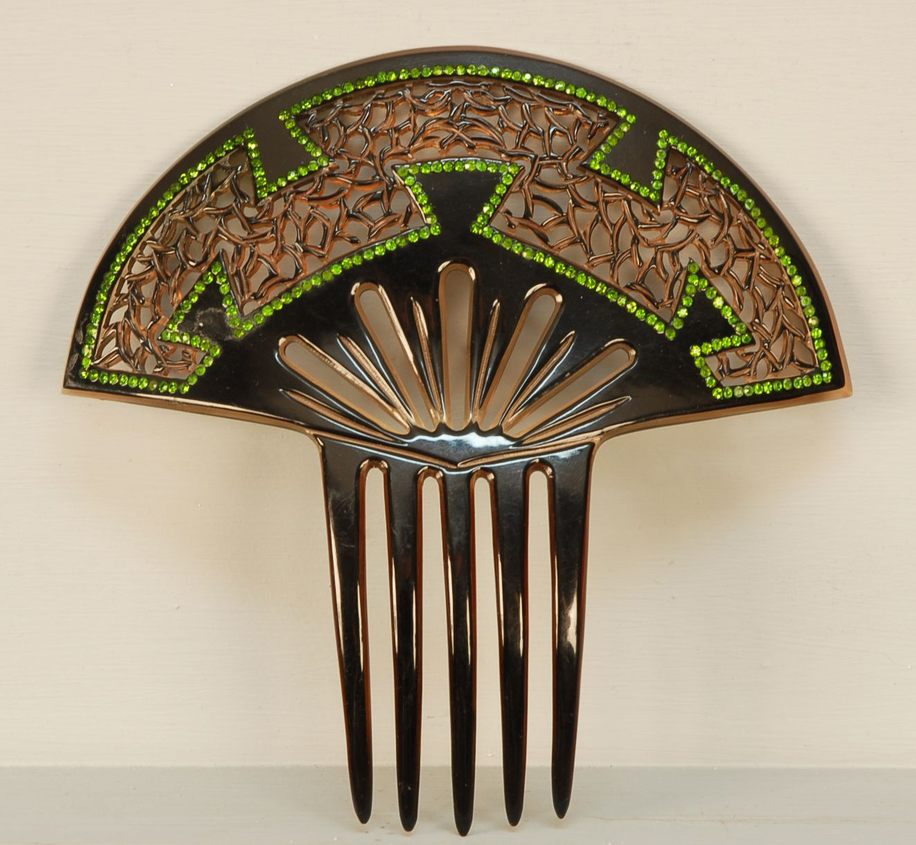 Hair Comb: pierced celluloid with green  sets and overlay.