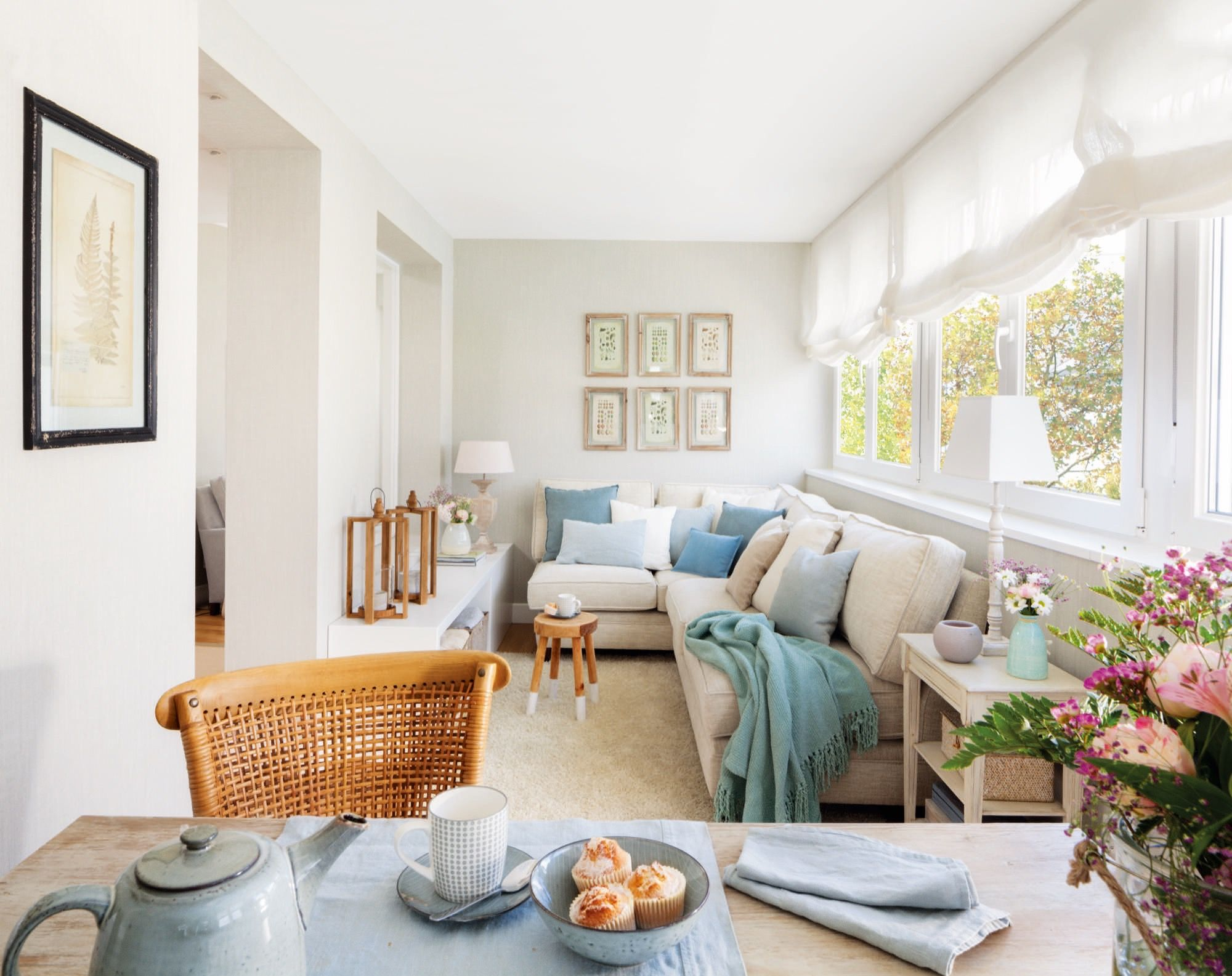 Sala de estar con sofa esquinero en tonos azul claro y for Decoracion piso blanco