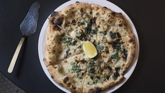 Littleneck clam pizza served with lemon at Pasquale Jones in New York, NY