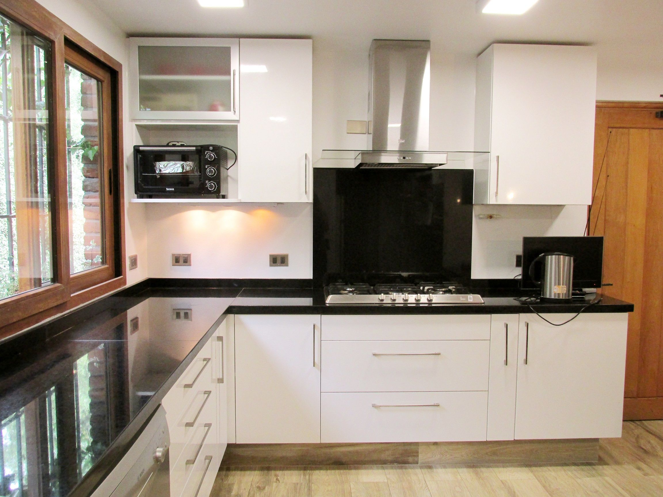 Muebles de cocina blanco brillante con cubierta de granito negro ...