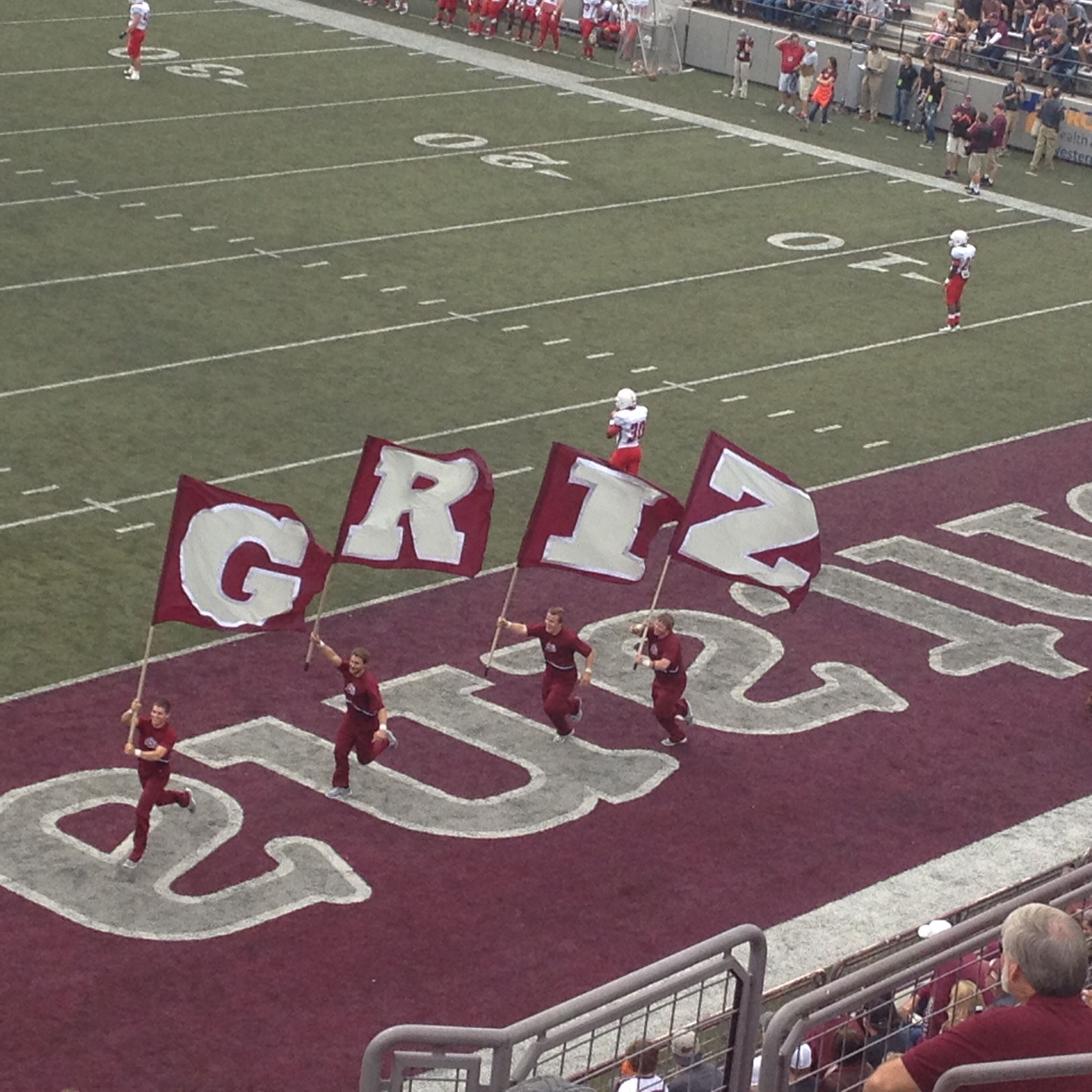 Montana Grizzly cheerleaders run through the endzone with the GRIZ flags. Go Griz!