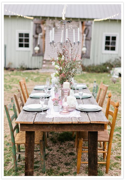 outside dining. wood table, wildflowers, white lights, and a chandelier