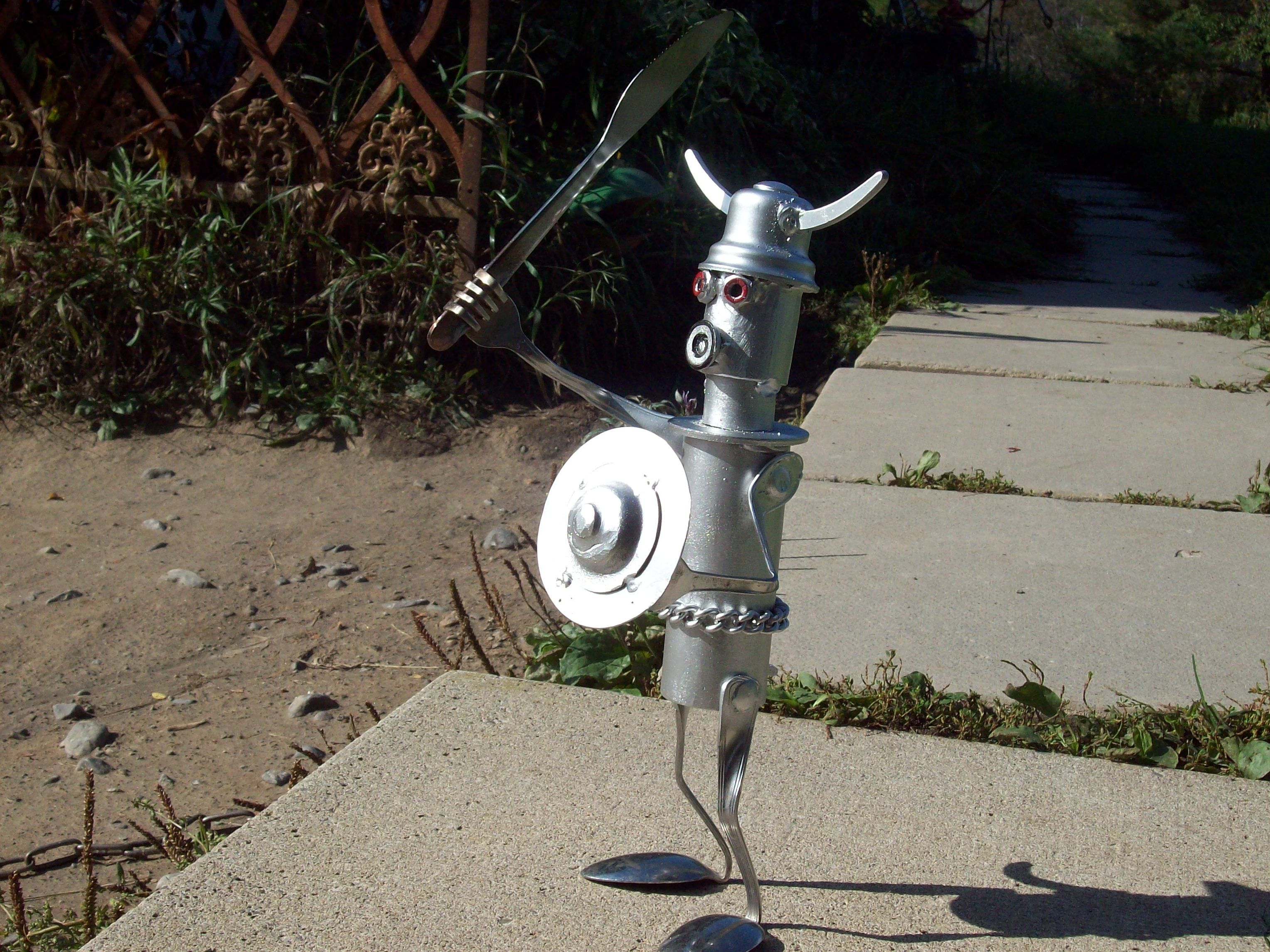 Small Iron Viking! Created by J.R.Hamm. Made out of recycled scrap metal and painted silver with red eyes.