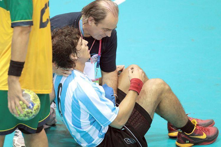 Diego Simonet, da Argentina, recebe atendimento médico após queda na partida final do handebol, contra a seleção brasileira