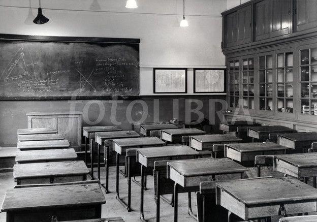 Klasserom på 1950 tallet. tre-pulter der du kunne åpne borplata og ha bøker eller andre ting i. Stoler og pulten hang saman.