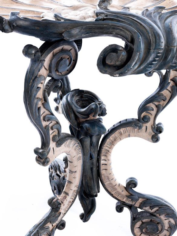 Holz, geschnitzt und weiß sowie blau gefasst. Die Tischplatte reliefiert geschnitzt in Form einer Muschel, die aus Blattwerk herauszieht und auf drei S-bogige ...