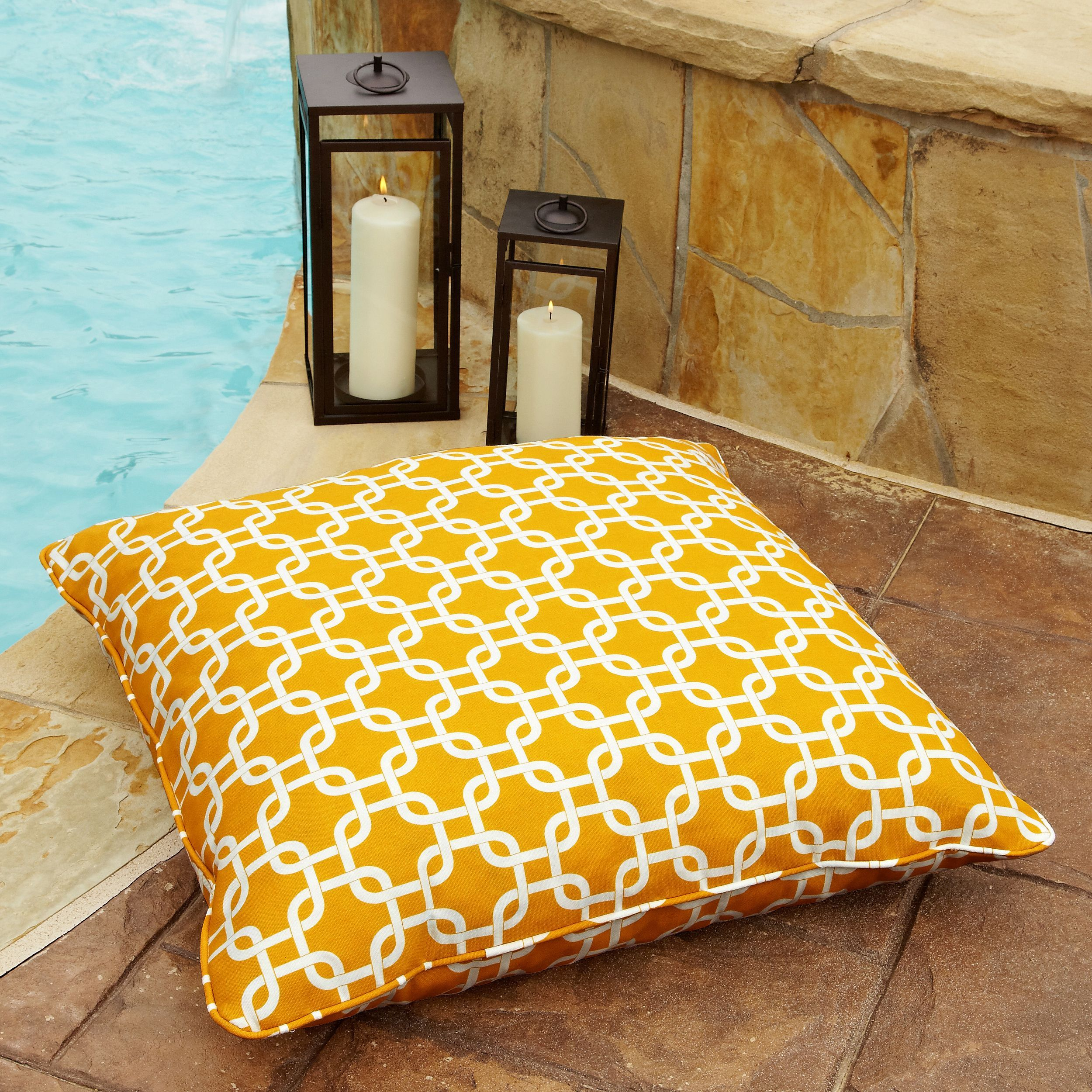 Fun interlocking squares decorate this white and yellow square floor pillow with matching cording. Made from polyester that is resistant to stains and fading, this large comfortable pillow is perfect for any outdoor pool deck or patio.