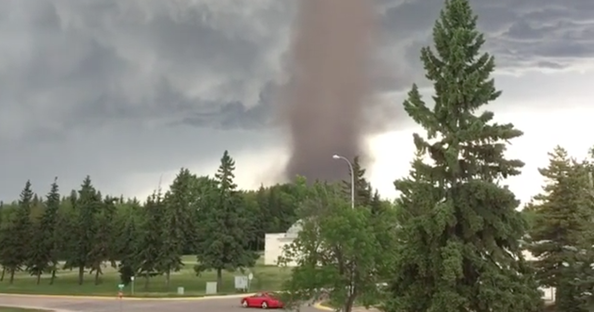 Very determined man mows the grass as a tornado swirls nearby