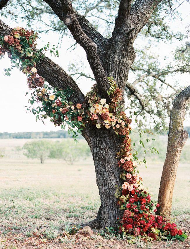 Mit Blumen geschmückter Baum als individuelle Dekoration für die Herbsthochzeit