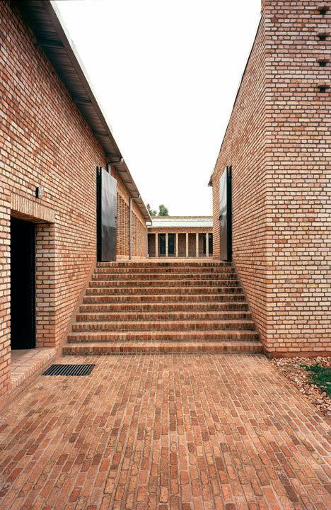 Red brick buildings wrap around an elevated piazza at this education centre in Rwanda