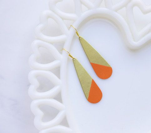 "Large rounded pieces of raw brass have been hand-painted in an edgy pattern. The color is a lovely shade of bright tangerine.  Each piece measures about 2"" and dangles from a gold, copper, or silver toned earring wire.  If you are a fan of our standard color dipped brass earrings, note that the..."