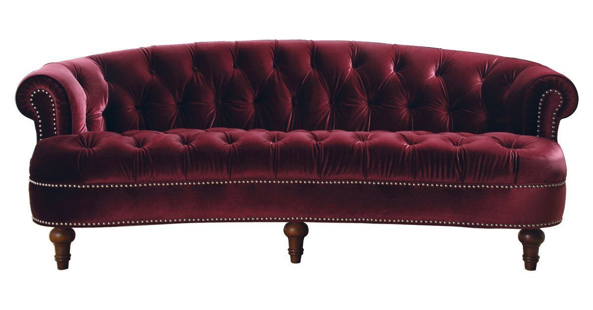 This luxurious tufted sofa is upholstered in richly hued red ...
