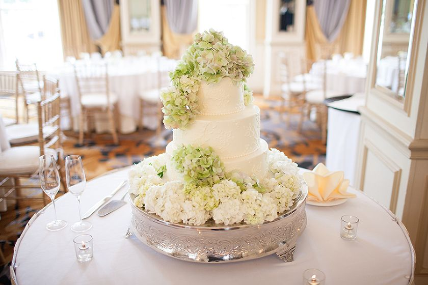 Beautiful three tiered white brides cake with white and green hydrangeas on silver cake stand - Photo by Victor Rosas Photography