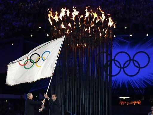 President of the International Olympic Committee Jacques Rogge, left, hands the Olympic flag to Rio de Janeiro's mayor Eduardo Paes during the Closing Ceremony at the 2012 Summer Olympics, Sunday, Aug. 12, 2012, in London. (AP Photo/Matt Dunham)  LONDON, ENGLAND - AUGUST 12: Brian May of Queen perfor