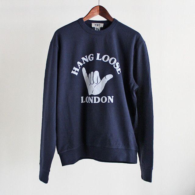 """英国ブランドYMCの""""Hang Loose London!"""" スウェット。 Hang Looseとは、""""ゆったりと行こう!""""、""""気楽に人生を楽しもう!""""というニュアンスを持つ言葉。カラーはネイビーにホワイトのグラフィックプリント。素材は、プレミアムコットンを使用したループバック・ジャージィ。"""