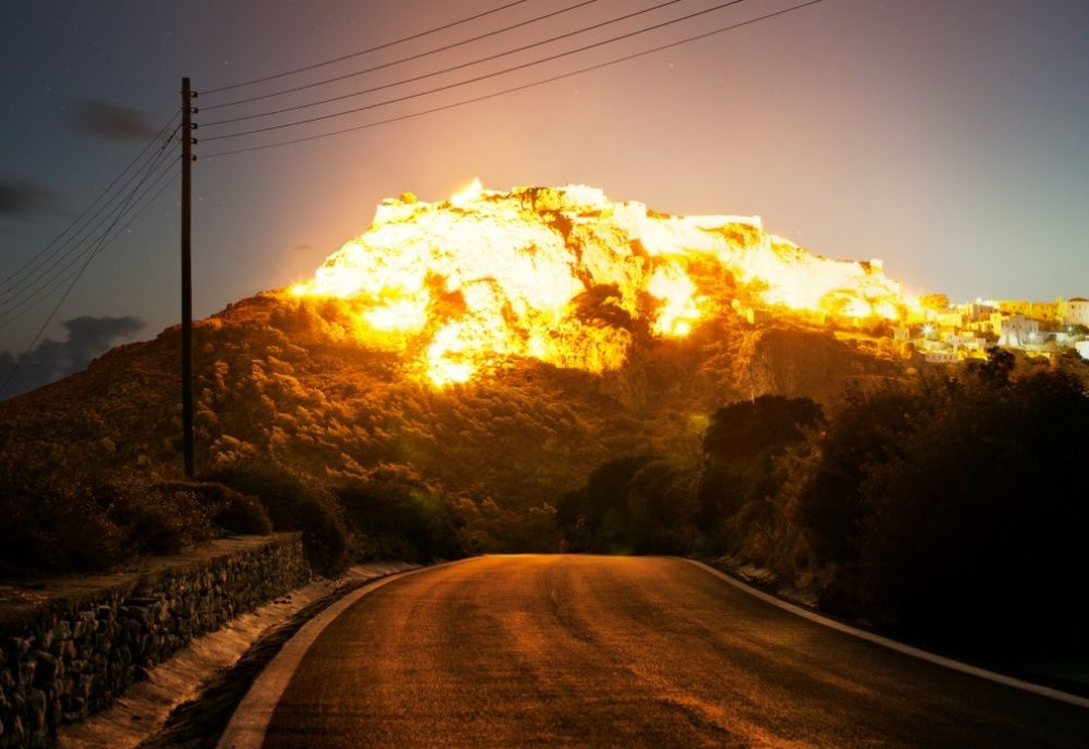 Time exposure of village on hill at night, giving impression of explosion.