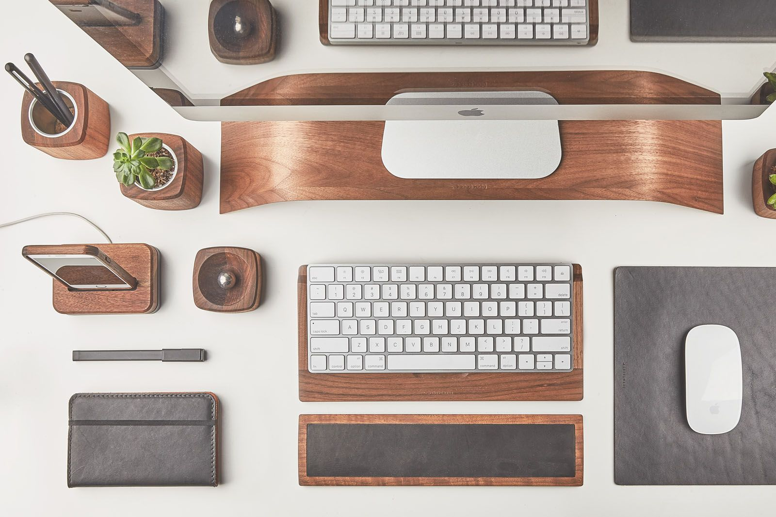 Top view of the walnut wood Grovemade Desk Collection with walnut keyboard tray, monitor stand, pen cups, desk lamps, planter, leather mouse pad, leather wrist pad.