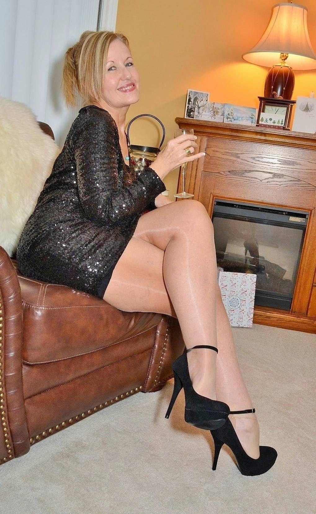 Beautiful lady sitting on sofa putting on stockings, healthy legs, varicose stock photo