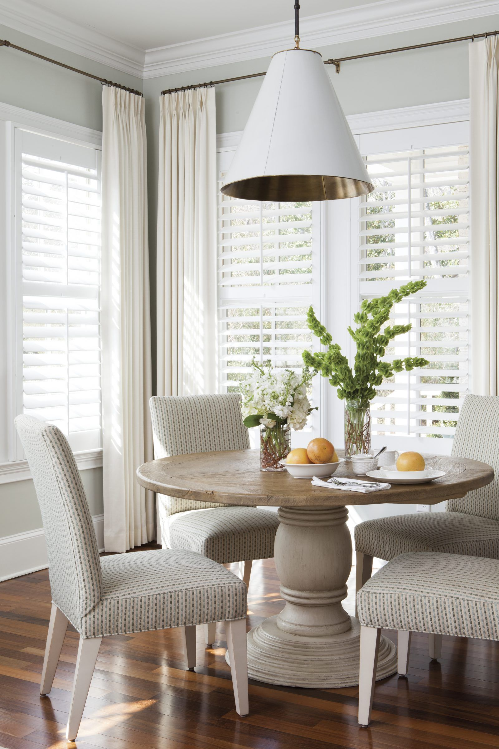 Bright dining nook + round wood dining table + upholstered