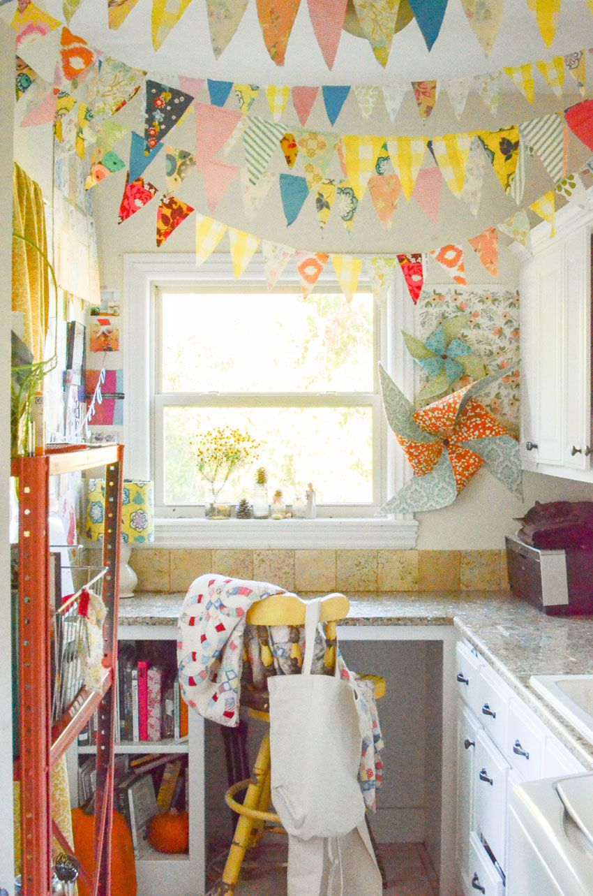 Bright and happy Craft Room. String a fabric bunting across your ceiling for a cheerful feel to your creative studio! Love this idea!