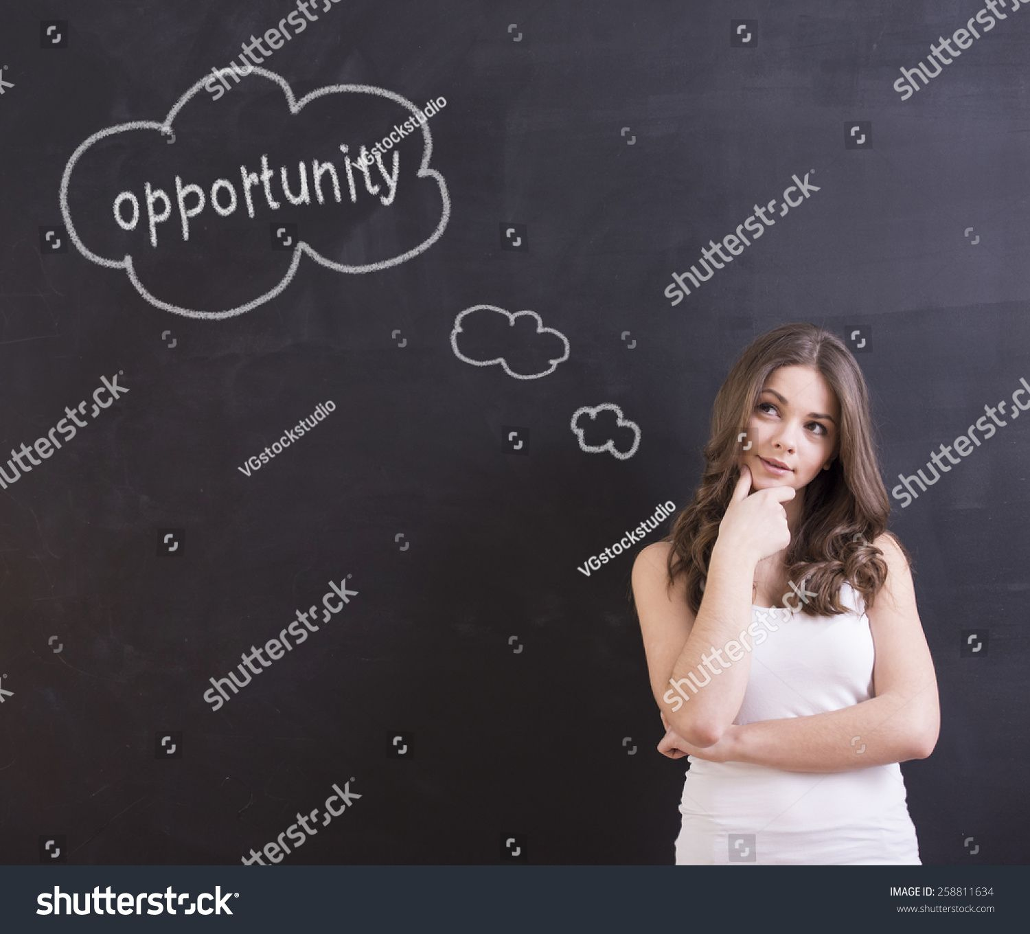 Young woman is standing in front of blackboard, looking away and thinking about opportunities. #Ad , #AD, #standing#woman#Young#front