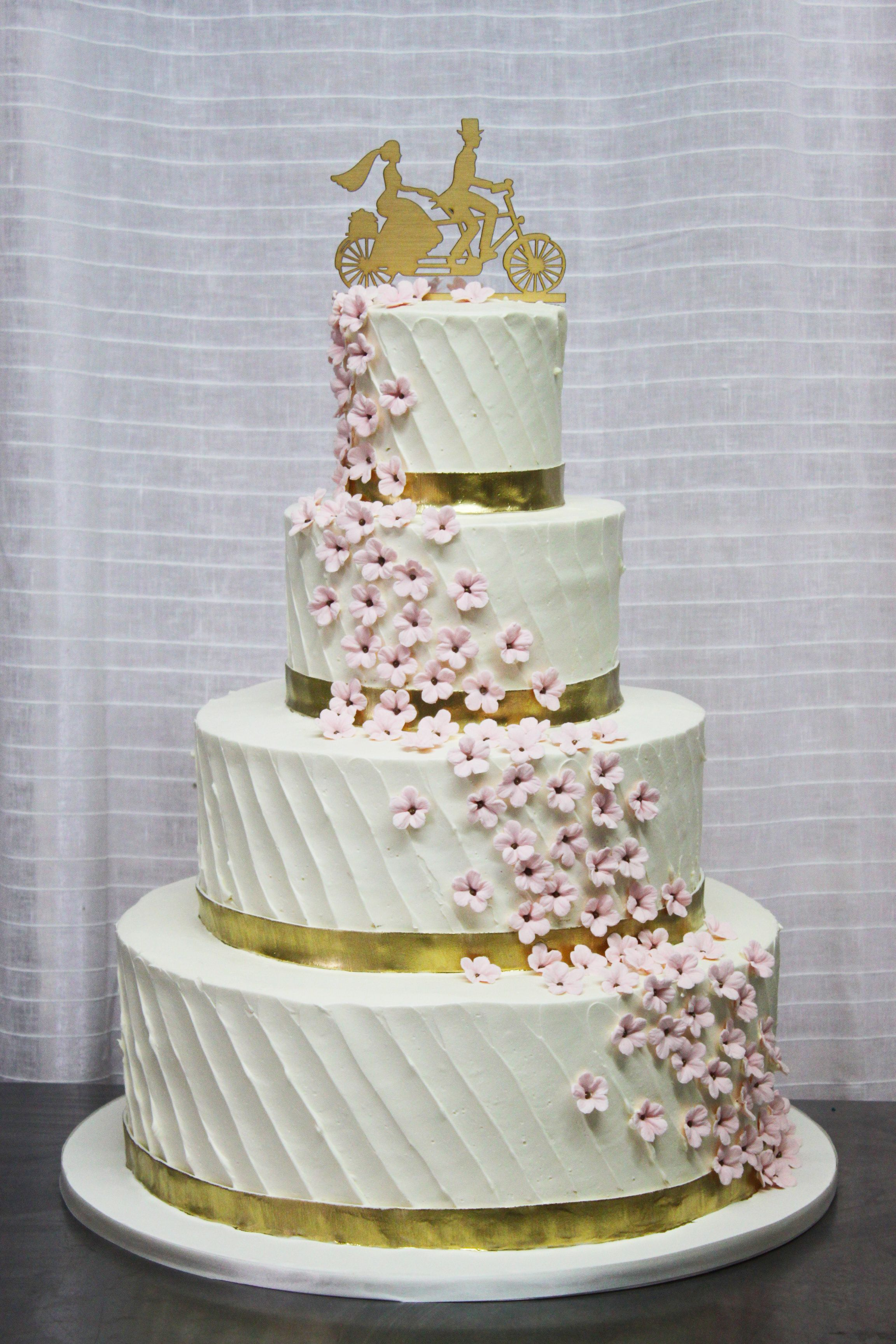 4 tier wedding cake frosted in a diagonal buttercream texture, with ...